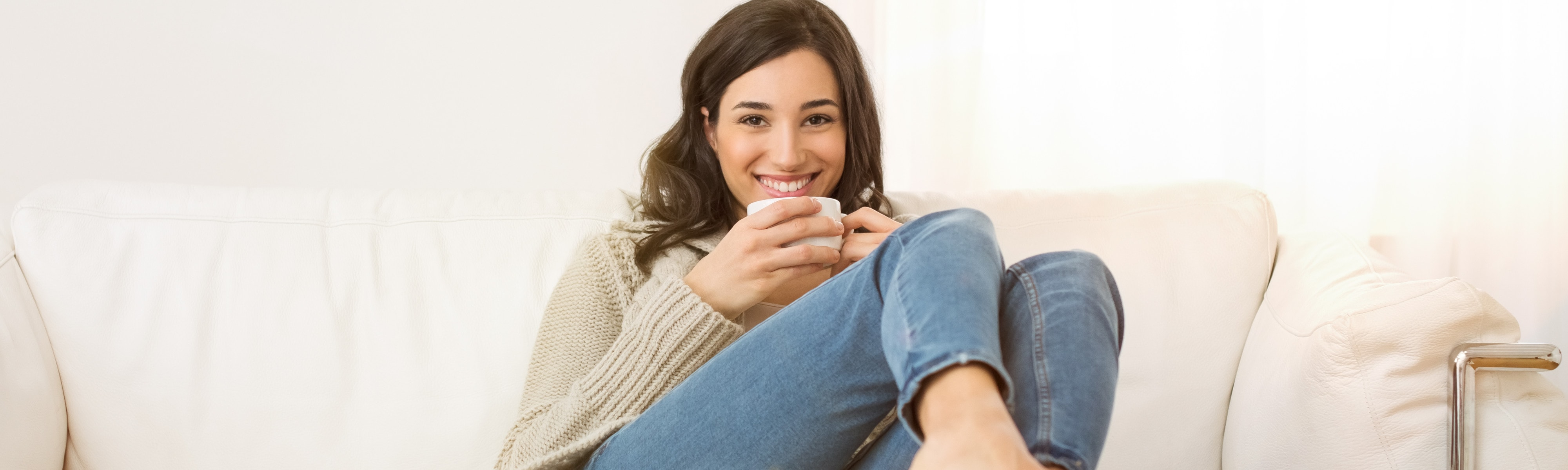 Woman on the couch with coffee.